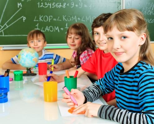 Група деца на маса пред дъска в училище