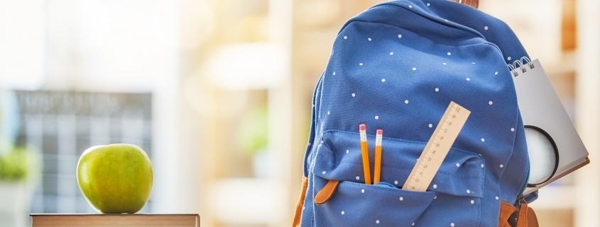 Подготовка за домашна работа- синя раница с моливи, тетрадка и учебници, поставени на бюро в стаята
